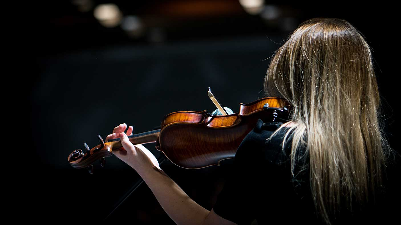 Girl playing the violin in concert hall