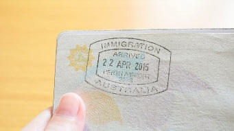 Hand holding passport with Australian immigration stamp for entering the country