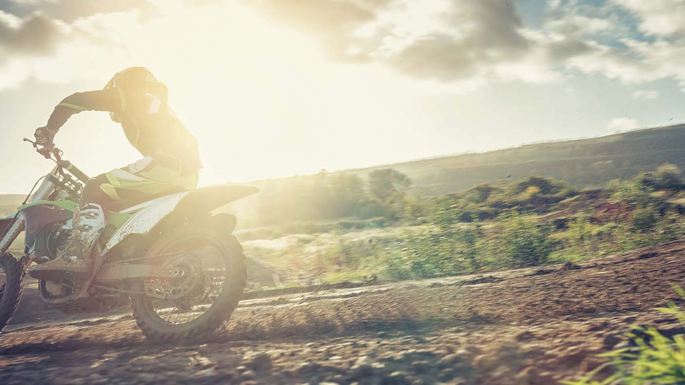 An close up image of a trail bike river on a dirt road