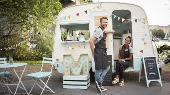 Stock image of a couple in front of their food van