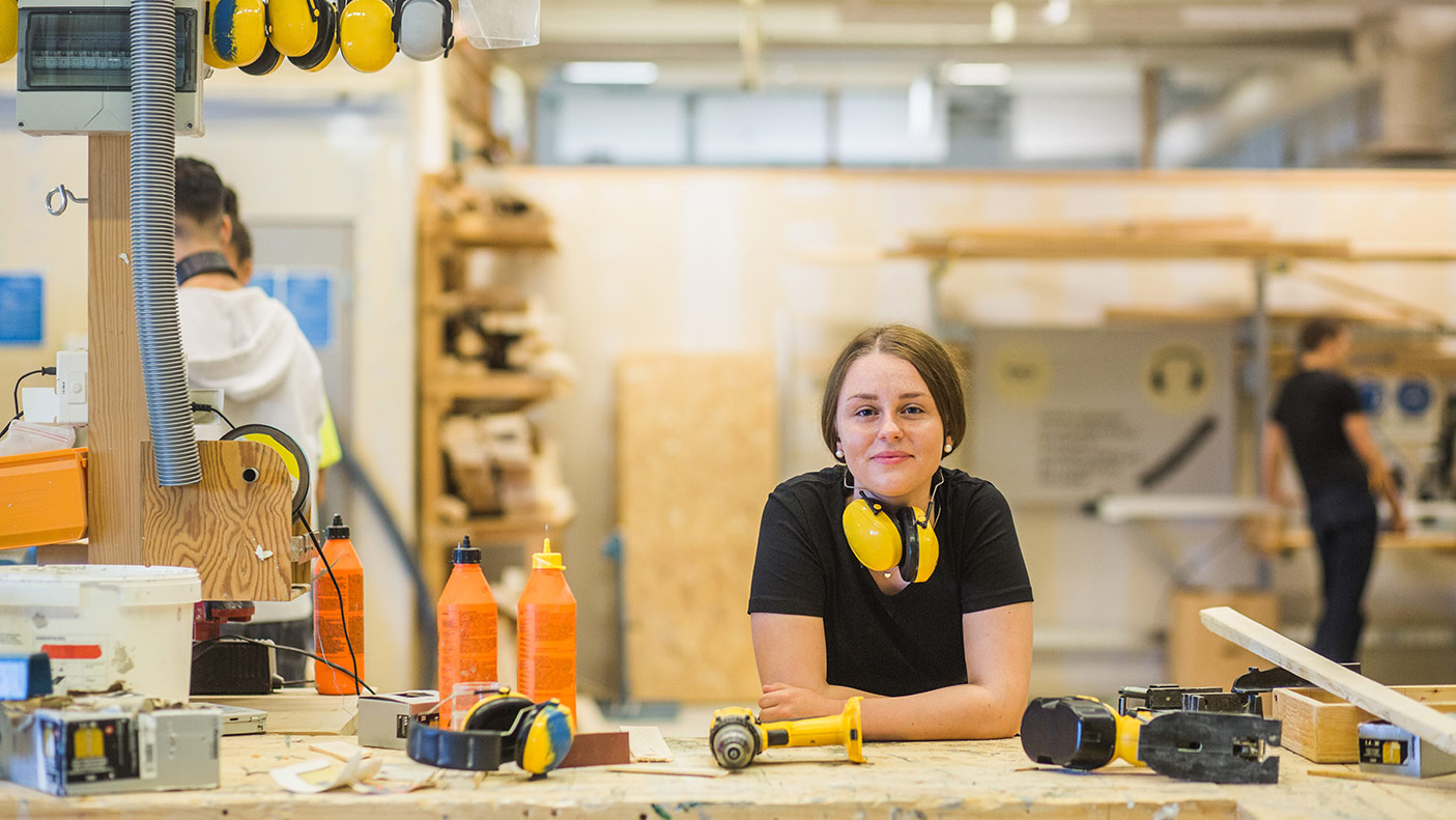 Portrait smiling young female carpentry trainee leaning on workbench with power tools at illuminated workshop - stock photo