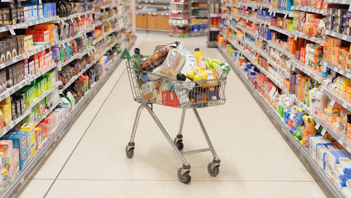 Full shopping cart in supermarket aisle - stock photo