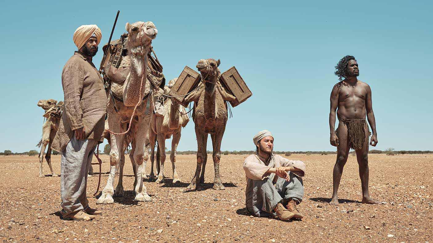 Still image from the film, The Furnace showing men and camels in a desert