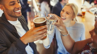 Enthusiastic friends toasting beer and wine glasses at bar