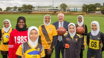 Minister Mick Murray with young women in various sporting unifroms