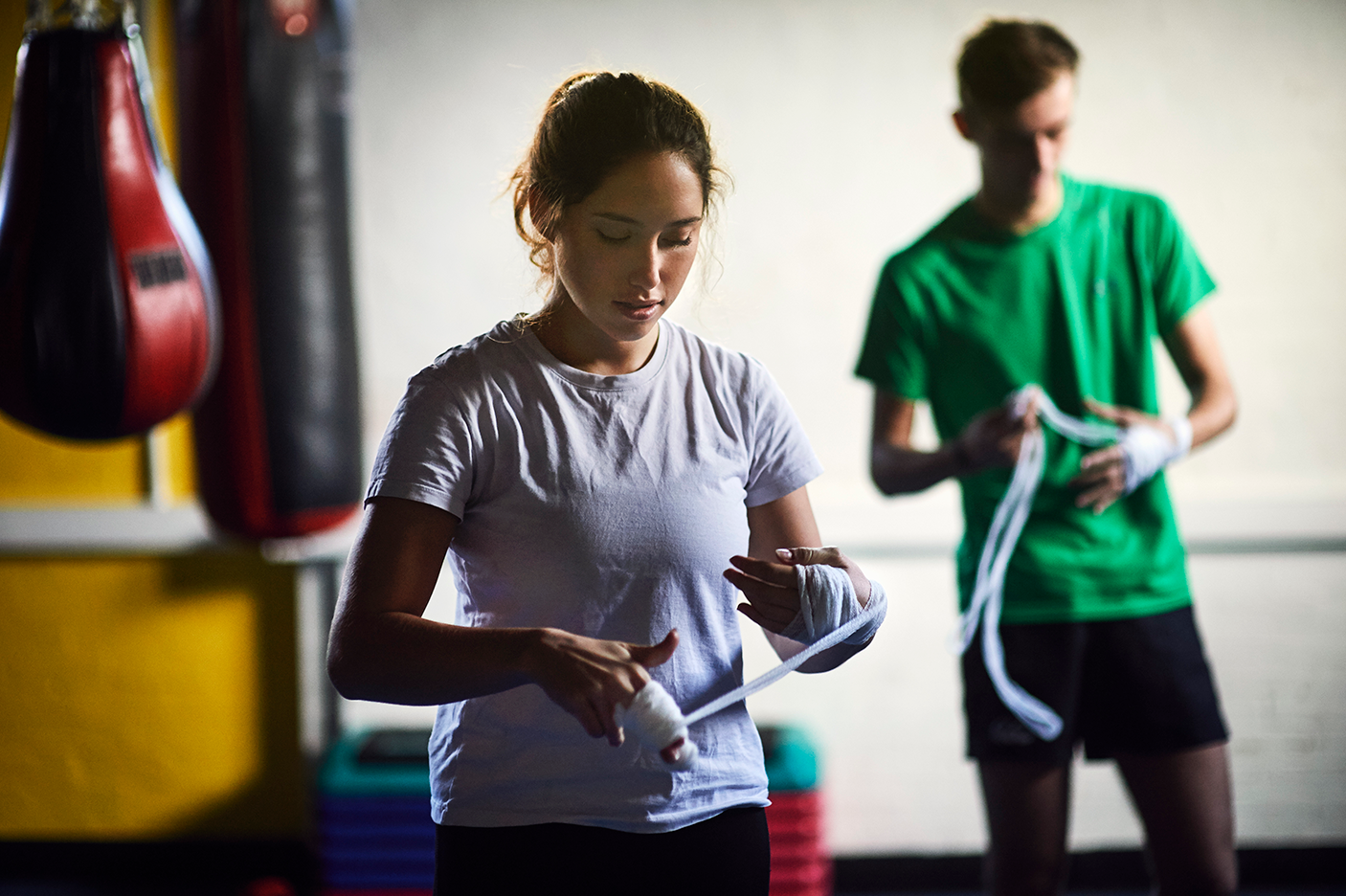 Young male and female boxers wrapping hands in bandages - stock photo