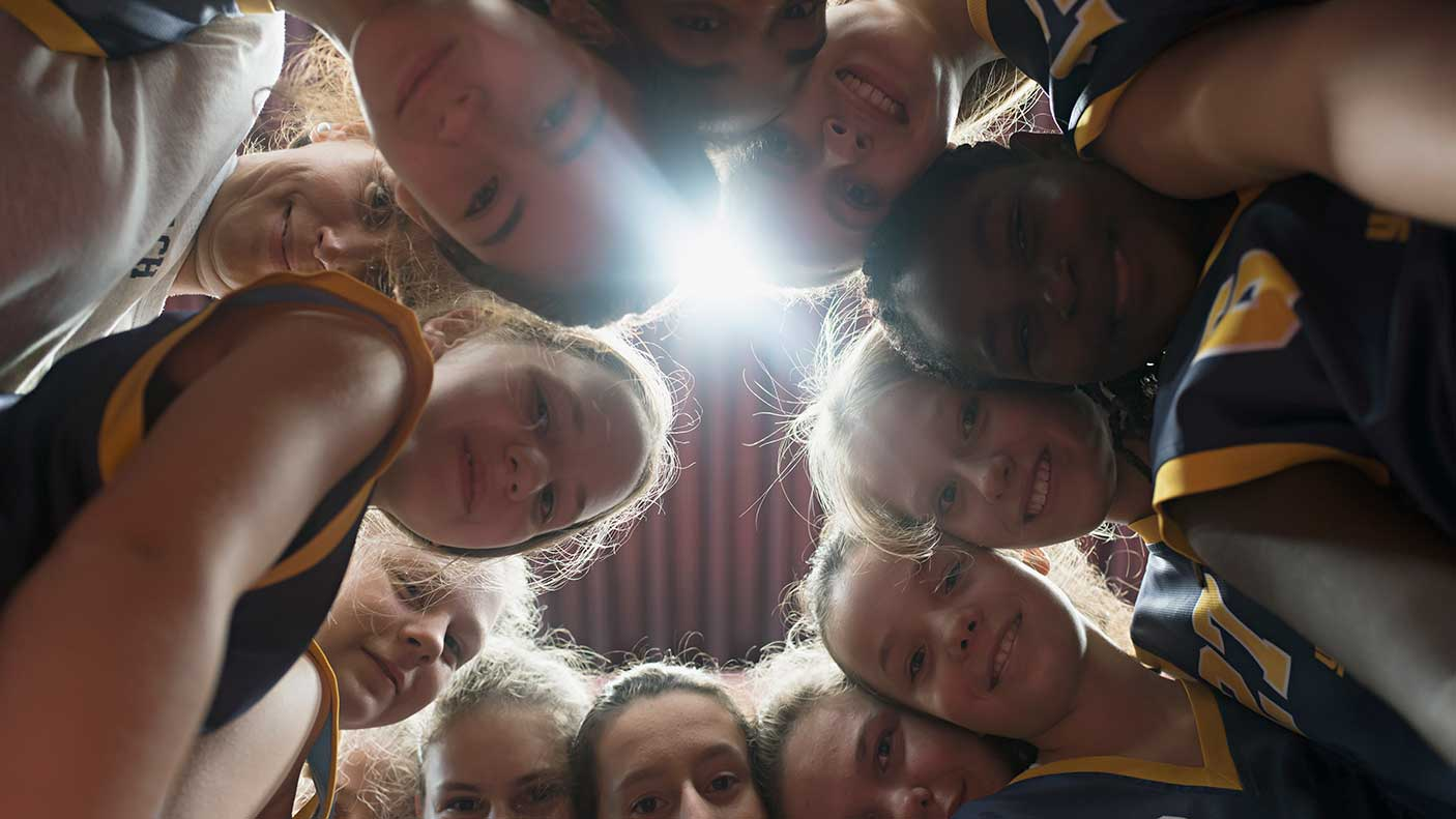 Female basketball players and coach huddling together in circle. Image credit: Joos Mind, Getty Images