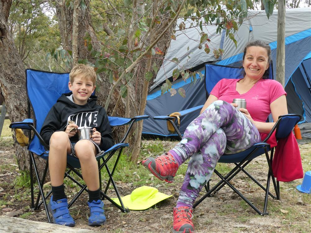 A mother and child sitting in camping chairs