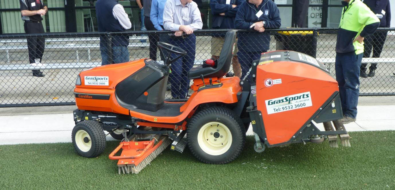 Ride on grooming and cleaning machine with petrol engine used to maintain synthetic turf.